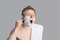 Young man shaving while yawning with eyes closed over colored background