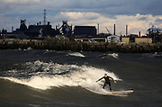 Bill Kobak of Chicago surfs in unusually high waves at Whihala beach in Whiting on Friday, September 30, 2011.