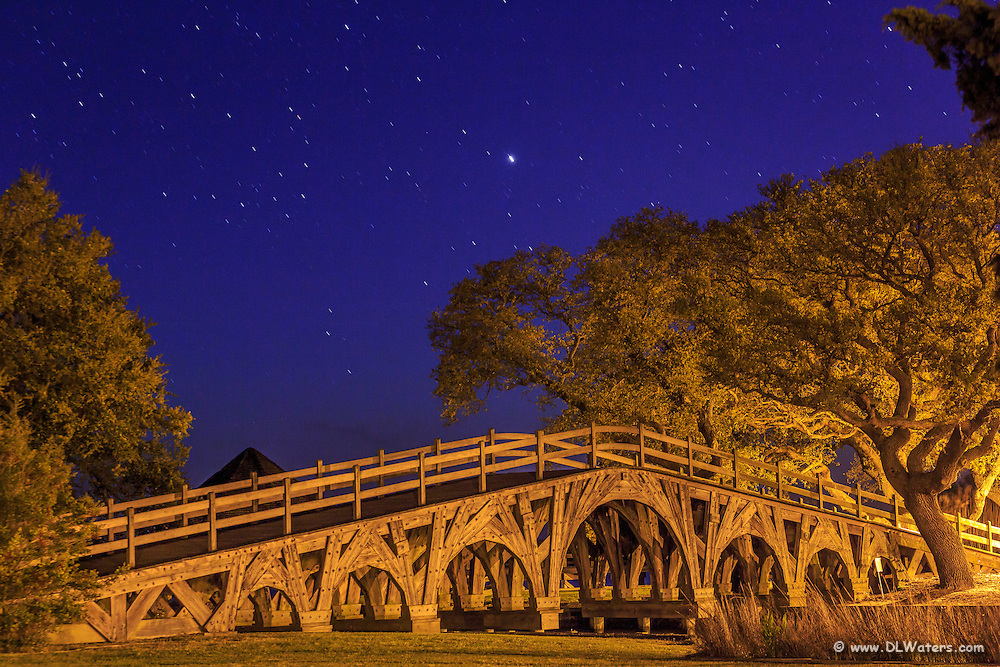 Bridge and live oaks between the Corolla lighthouse and the Whale Head Club at night.