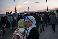 A woman is seen carring her child in the makeshift camp next to the Greek Macedonian border not far from the Greek village of Idomeni, Greece. FEDERICO SCOPPA/CAPTA