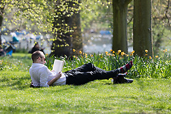 © Licensed to London News Pictures. 19/04/2018. London, UK. A man, who has removed his shoes relaxes with a book during hot weather in Regents Park in London at lunchtime today. Photo credit: Vickie Flores/LNP