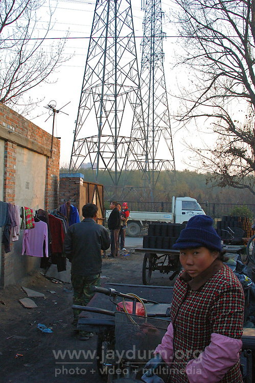 China, Beijing, Ping Fang Xiang, 2008. On the north side of Chao Yang Bei Lu outside the 5th Ring Road, a coal delivery woman observes the brick stamping process..