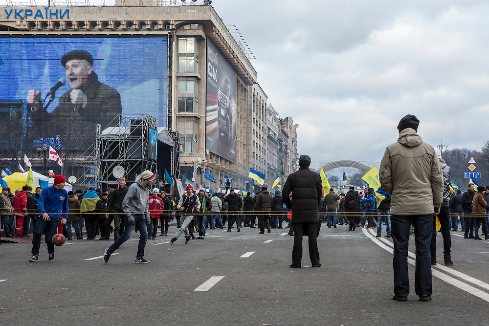 A live video of speakers on the main stage was shown on a large television screen on the side of the Trade Unions building as anti-government protesters played soccer in the street in Independence Square.