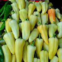 Yellow Peppers Display at Outdoor Market in Eger, Hungary<br /> Pick a bell pepper early in its life and it is green. Be patient for a few days or weeks and it may become yellow and mellower like these on display at a market in Eger, Hungary. I love their taste. But if it contains capsaicin, like the Hungarian wax pepper, then it is a chili pepper. They burn your mouth and sensitive skin.