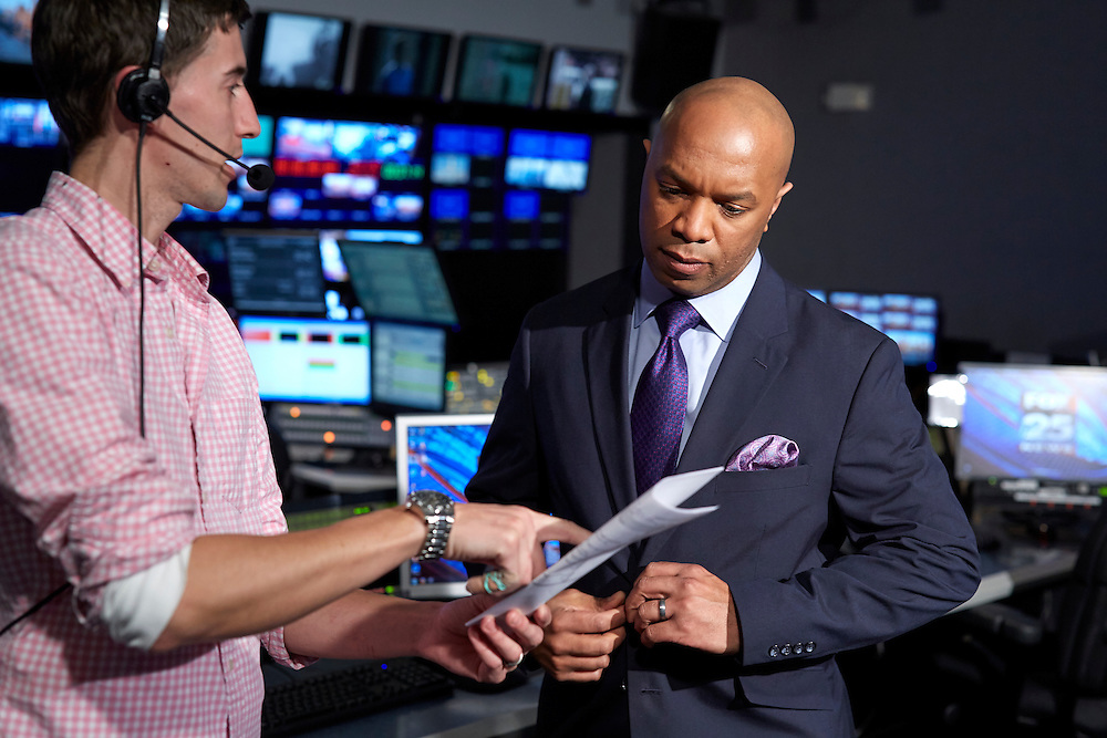 Dedham, MA 03/25/2015<br /> Fox 25 early morning anchor Daniel Miller talks with studio technician Joel Almeida inside the station's control room.<br /> Alex Jones / www.alexjonesphoto.com