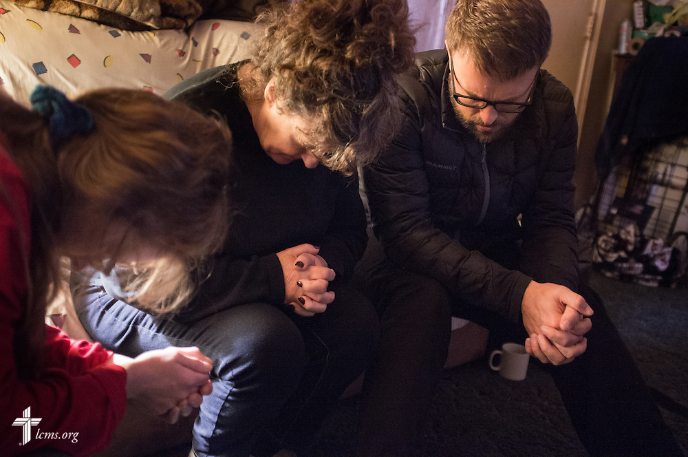 "The Rev. Adam DeGroot, new national missionary and pastor at Shepherd of the City Lutheran Church, a church plant and focus of Philadelphia Lutheran Ministries, prays with Kayla ""Keke"" Hiemenz (left) and Mildred Williams during a home visitation on Monday, Nov. 2, 2015, in Philadelphia.  LCMS Communications/Erik M. Lunsford"