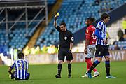 Referee Tony Harrington awards a yellow card to Kasey Palmer of Bristol City FC during the EFL Sky Bet Championship match between Sheffield Wednesday and Bristol City at Hillsborough, Sheffield, England on 22 December 2019.