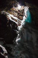 Jeff Mercier, a professional alpine climber as seen hanging on one ice tool during a rapid night ascent of Cascate di Lillaz icefall.