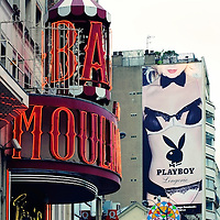 The entrance to the Moulin Rouge with red neon sign behind a poster of Playboy with a nude model  in Paris.