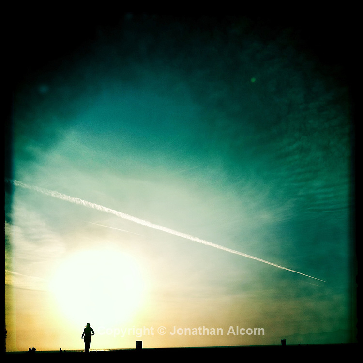 A woamn takes in the sunset in Venice Beach with a contrail in the sky