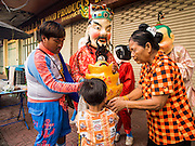 30 OCTOBER 2014 - BANGKOK, THAILAND: People donate money to Chinese dancers during the parade marking the start of the annual temple fair at Wat Saket. Wat Saket is on a man-made hill in the historic section of Bangkok. The temple has golden spire that is 260 feet high which was the highest point in Bangkok for more than 100 years. The temple construction began in the 1800s in the reign of King Rama III and was completed in the reign of King Rama IV. The annual temple fair is held on the 12th lunar month, for nine days around the November full moon. During the fair a red cloth (reminiscent of a monk's robe) is placed around the Golden Mount while the temple grounds hosts Thai traditional theatre, food stalls and traditional shows.   PHOTO BY JACK KURTZ