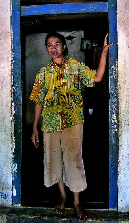 A woman looks out from her doorway on Lembata Island, Indonesia.