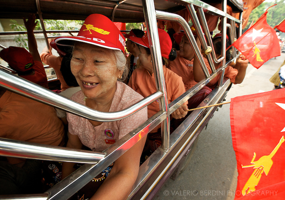 A woman with 'thanaka', the traditional Burmese make-up parades with NLD supporters. Myanmar, 2012.