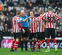 NEWCASTLE, ENGLAND - Sunday, March 4, 2012: Sunderland players surround referee Mike Dean after he sent off Stephane Sessegnon during the Premiership match against Newcastle United at St. James' Park. (Pic by David Rawcliffe/Propaganda)