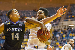 Jan 26, 2016; Morgantown, WV, USA; West Virginia Mountaineers guard Tarik Phillip (12) grabs a rebound over Kansas State Wildcats guard Justin Edwards (14) during the first half at the WVU Coliseum. Mandatory Credit: Ben Queen-USA TODAY Sports