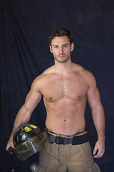 Shirtless muscular fireman holding his helmet