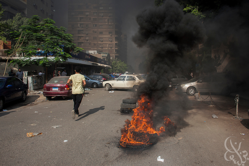 A man runs past burning tires on the edge of the Rabaah al-Adawiya protest camp in Nasr City during an August 14, 2013 Ministry of Interior/Police operation to clear the protest by force. The assault, which began at 7am with police moving in to seal the surrounding streets included tear gas and live fire, and there are reports of large numbers of killed and wounded protesters.
