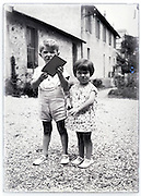 summer two children together in backyard vintage 1900s