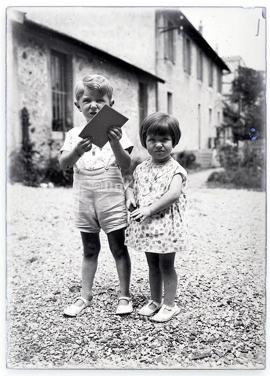 summer two children together in backyard vintage 1900s