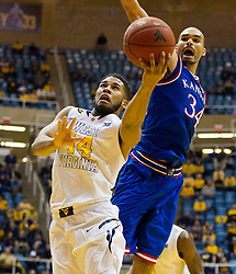 West Virginia Mountaineers guard Gary Browne (14) is blocked by Kansas Jayhawks forward Perry Ellis (34) during the second half at the WVU Coliseum.