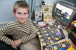 Boy with Autism sitting at desk with his collection of Harry Potter Top Trump playing cards,