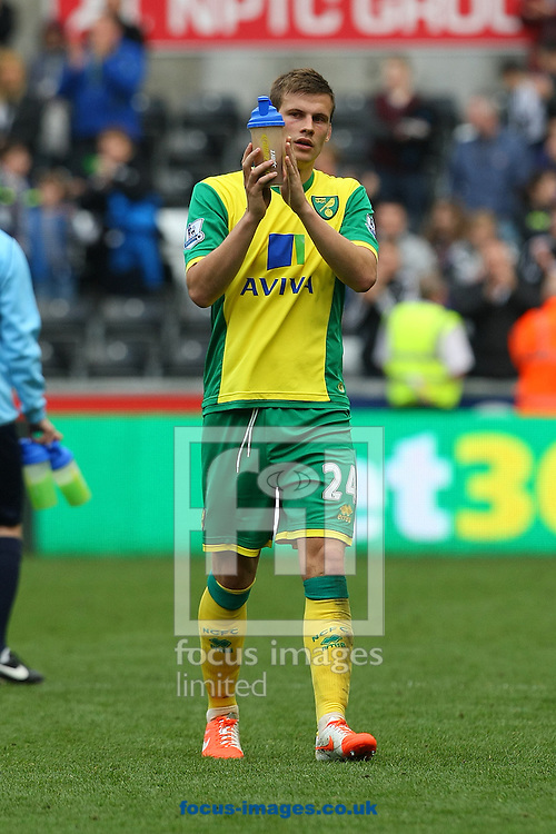 A dejected looking Ryan Bennett of Norwich applauds the traveling support at the end of the Barclays Premier League match at the Liberty Stadium, Swansea<br /> Picture by Paul Chesterton/Focus Images Ltd +44 7904 640267<br /> 29/03/2014
