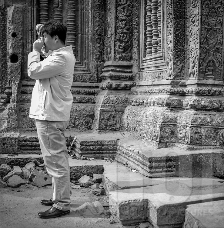 Tourist stands beside a stone temple of Angkor as he photographs the ruins, Siem Reap, Cambodia, 2005, Southeast Asia