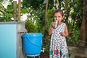 After dinner, Asmita drinks water from her family's biosand filter.