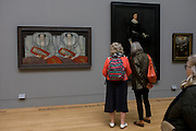 Three women admire Tudor portraits of Elizabethan nobility in Tate Britain, London.