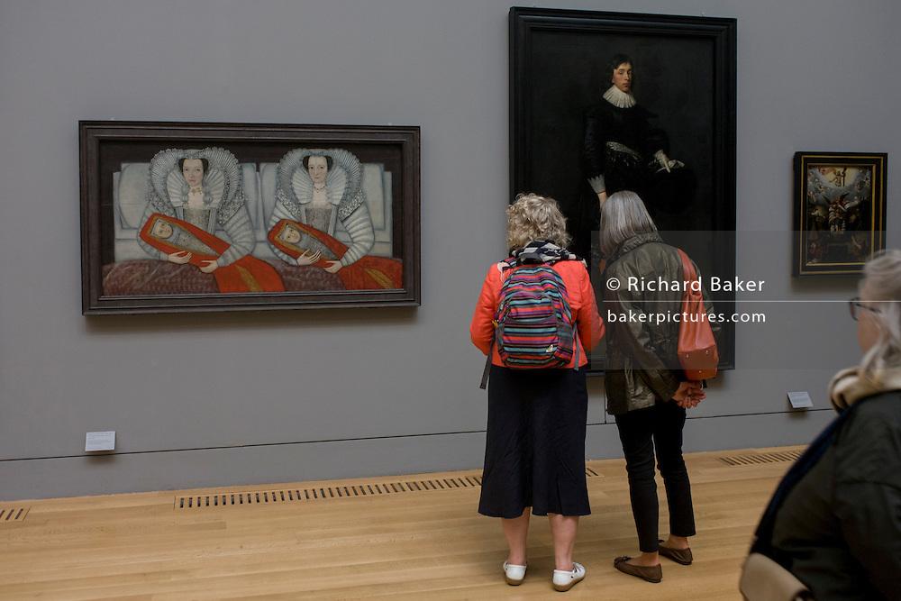 Three women admire Tudor portraits of Elizabethan nobility in Tate Britain, London.