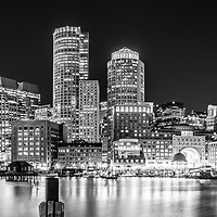 Boston skyline at night black and white panorama photo with the Boston Harborwalk waterfront, downtown Boston skyscrapers and Nothern Avenue Bridge. Panorama photo ratio is 1:3.