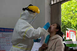XIANGYANG, April 18, 2020  A worker in protective suit collects a swab from a teacher for nucleic acid test in Fancheng District of Xiangyang City, central China's Hubei Province, April 18, 2020. In order to ensure the safety of teachers and students, all teachers in Xiangyang City are required to accept nucleic acid tests before they return to work. (Photo by Xie Jianfei/Xinhua) (Credit Image: © Xie Jianfei/Xinhua via ZUMA Wire)