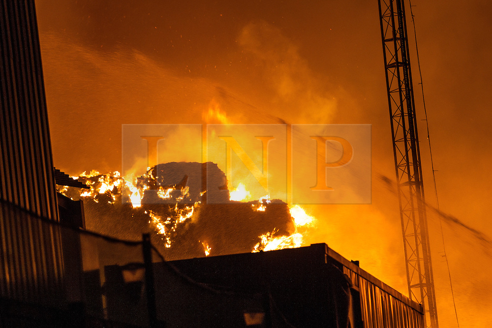 © Licensed to London News Pictures . 21/08/2013 . Stockport , UK . Large bales of recyclable material are alight . Firefighters tackle a large blaze at the J25 Recycling Centre in Bredbury , Stockport this morning (Wednesday 21st August 2013) where a building and bales of recyclable material are alight . The fire , which started late last night (20th August) is being tackled by more than 50 fire crew . The site , which is adjacent to a branch of Morrisons Supermarket and McDonalds , is off Junction 25 of the M60 motorway , exits for which are closed in both directions . Photo credit : Joel Goodman/LNP