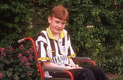Portrait of young boy with disability; who is wheelchair user; in garden smiling,