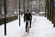 Een man op een vouwfiets rijdt op de Zijpendaalseweg in Arnhem door de sneeuw.<br /> <br /> A man on a folding bike is cycling at the Zijpendaalseweg in Arnhem in the snow.