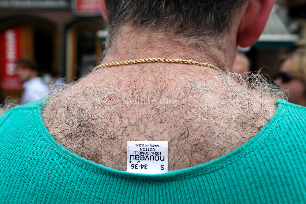 very hairy back of male person with clothing label sticking out from under t shirt