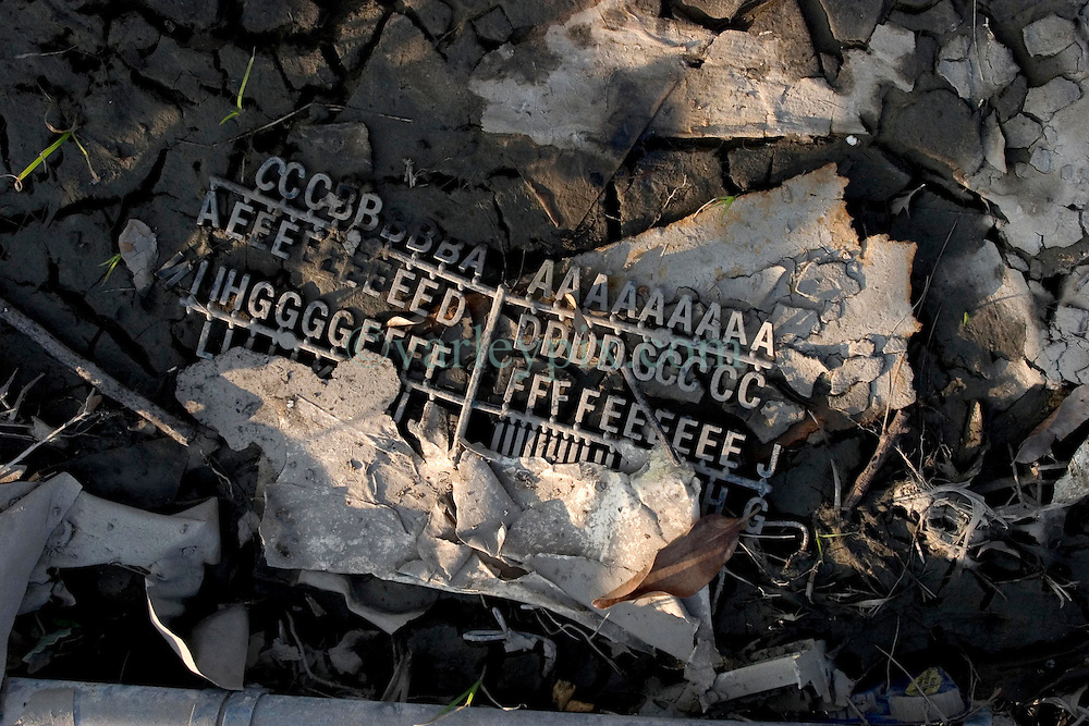 30 Sept, 2005.  New Orleans, Louisiana. Lower 9th ward. Hurricane Katrina aftermath. <br /> The remnants of the lives of ordinary folks, now covered in mud as the flood waters remain.  a child's alphabet letters lie in the dirt.<br /> Photo; ©Charlie Varley/varleypix.com