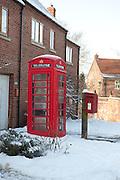 A red UK Royal Mail post box attached to a wooden post in the snow next to a traditional red BT telephone box.