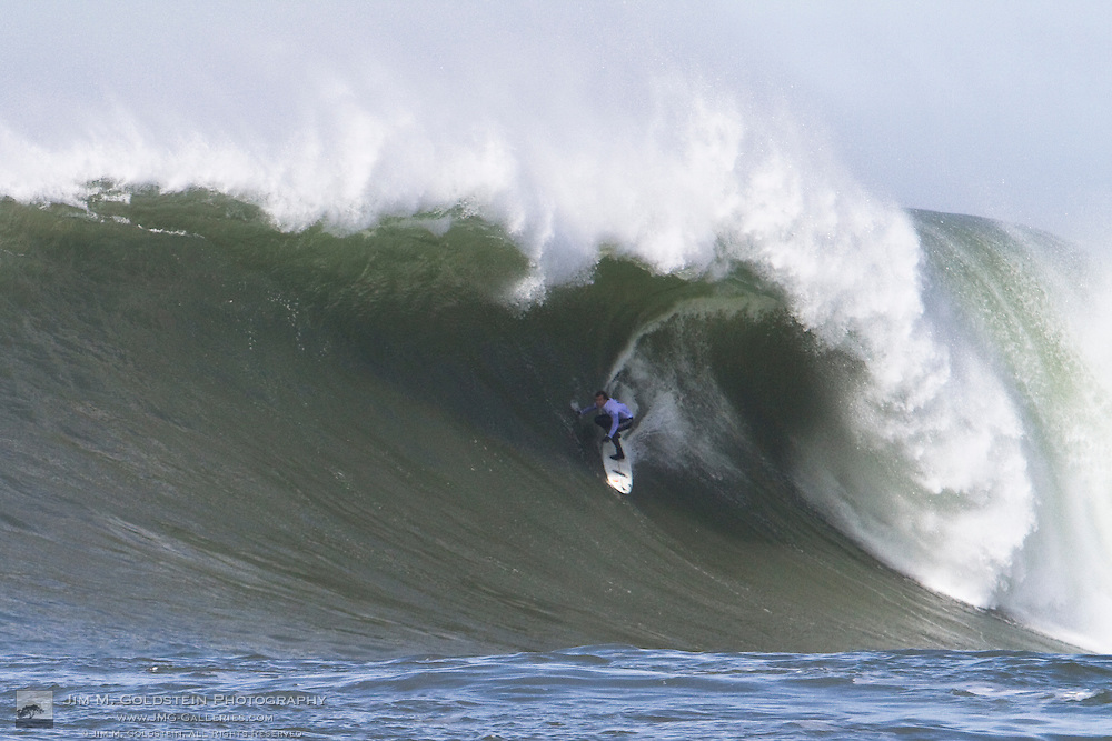 Carlos Burle under the lip of a giant wave as he gets tubed at the 2010 Mavericks Surf Contest