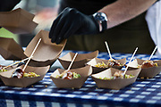 A cook from Vanguard places trays for their Filipino chicken skewers during the 4th annual Yum Yum Fest held at Breese Stevens Field, Sunday, August 6, 2017.