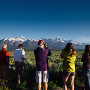 Teten Science Schools tour participants watch a herd of elk forage in the early morning hours. (Greg Peck, Matthew Bart, Sean Baker, Maura Bushior, Katie-Cloe Stock, Tracy Logan, dawson-Guide) Tetons in the background.