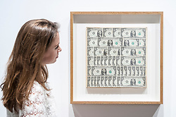 "© Licensed to London News Pictures. 08/06/2015. London, UK. A Sotheby's staff member looks at ""Dollar Bills"" by Andy Warhol (est. £120k - £180k), at the preview of ""To the Bearer on Demand"", a private collection of 21 works inspired by the US dollar, including Andy Warhol masterpieces, which will be auctioned on 1 and 2 July.  The collection is estimated to realise £50 million. Photo credit : Stephen Chung/LNP"