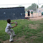 A young boy practices his throwing against the dugout wall  during the Norwalk Little League baseball competition at Broad River Fields,  Norwalk, Connecticut. USA. Photo Tim Clayton