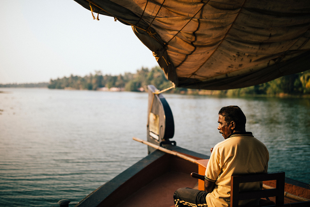 Alleppey, India -- February 20, 2018: A man navigates a boat through the backwaters of Kerala, India.