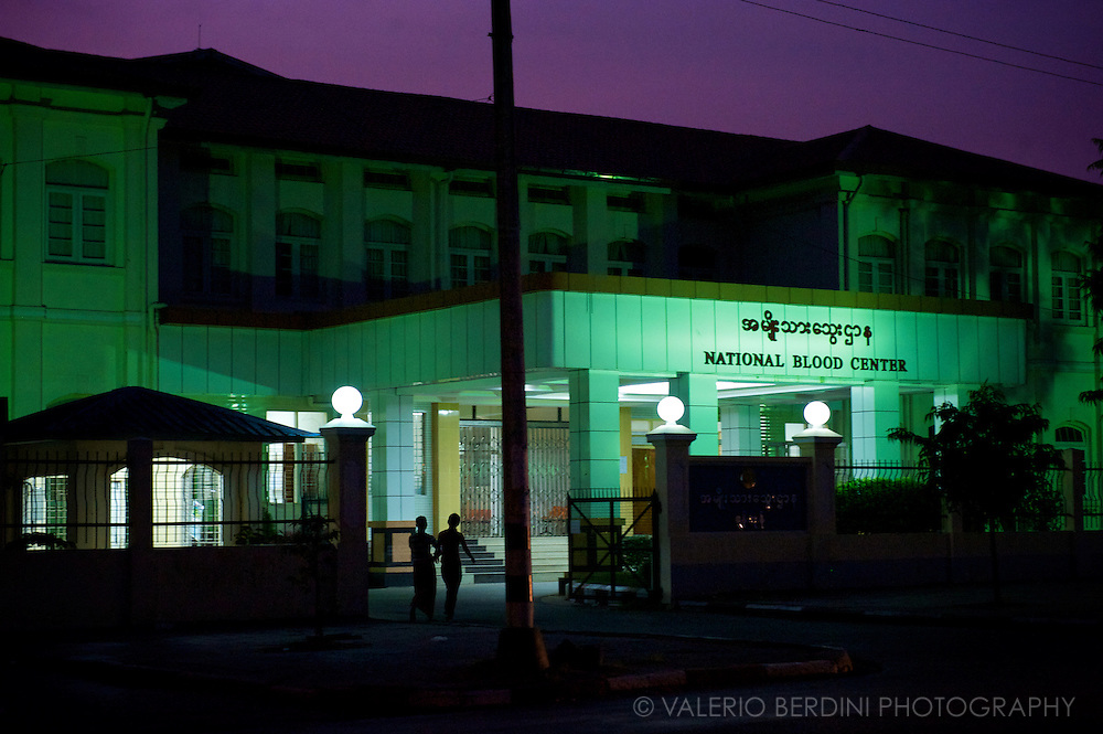 A couple walks next to the National Blood Center at night. Burma Health service ranked second-worst in the world from a WHO report.