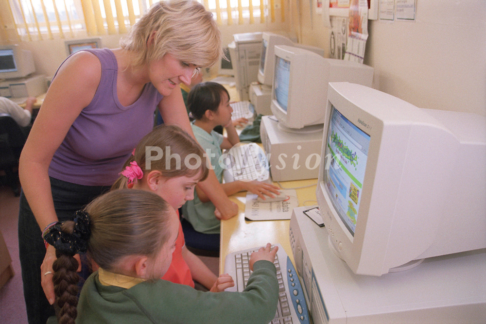 Primary school teacher helping pupils to use computers during Information and Technology lesson,