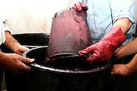 Tre contadino fanno un travaso del mosto da una tinozza all'altra. Questo mosto verrà messo a riposo per una notte con le bucce affinchè acquisti il tipico colore rosso.