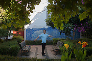 A Chinese man performs early morning exercises and stretches in front of Azulejo tiles in a city park, Lisbon Portugal.