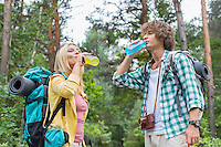 Young hiking couple drinking energy drinks in forest