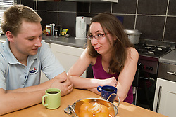 Couple sitting at the kitchen table chatting,